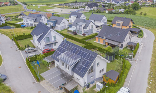 A high angle shot of private houses with solar panels on the roofs
